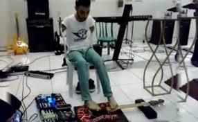 Joven sin brazos toca la guitarra electrica con los pies